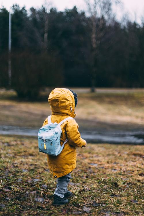 enfant en manteau jaune qui explore